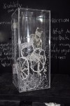 Photography of artwork from A Thousand Threads collection. Image description includes threads shaped into a wheelchair incased in a glass vase.  A Thousand Threads copyright Elaine Steward, 2016